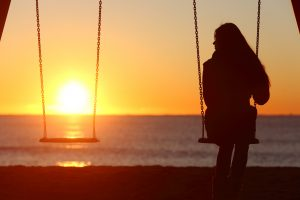 Woman sits alone on swing at sunset considering her prenuptial agreement