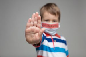 Child with coronavirus mask on holding out his hand