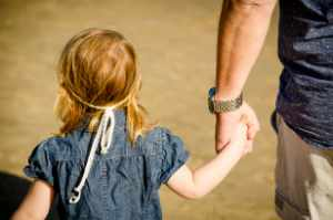 Child holding a man's hand