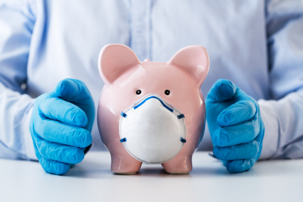 Gloved hands protecting a piggy bank