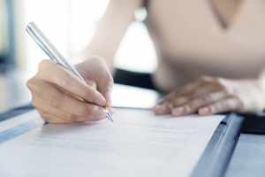 woman signing an agreement
