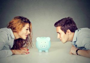 man and woman looking at piggy bank