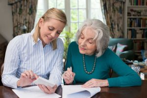elderly woman signing power of attorney