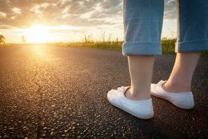 Woman in white sneakers standing on asphalt road towards sun