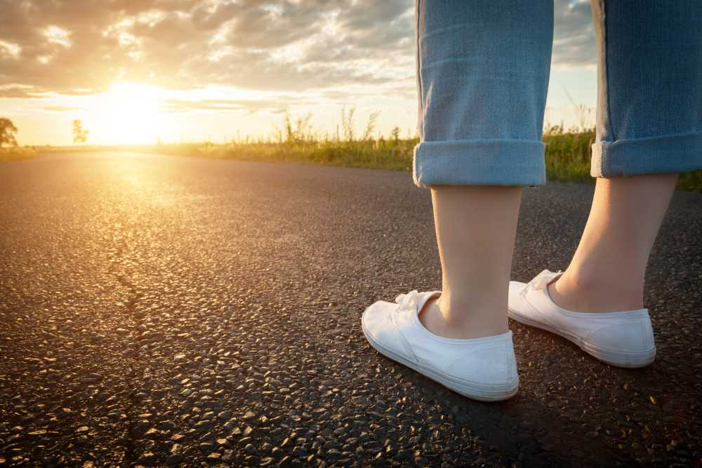 Woman in white sneakers standing on asphalt road towards sun