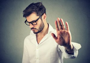 annoyed angry man with bad attitude giving talk to hand gesture