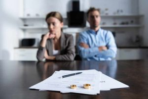 couple sitting at table with divorce documents